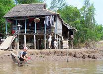 huisje met mensen aan oever - Mekong Delta - Vietnam