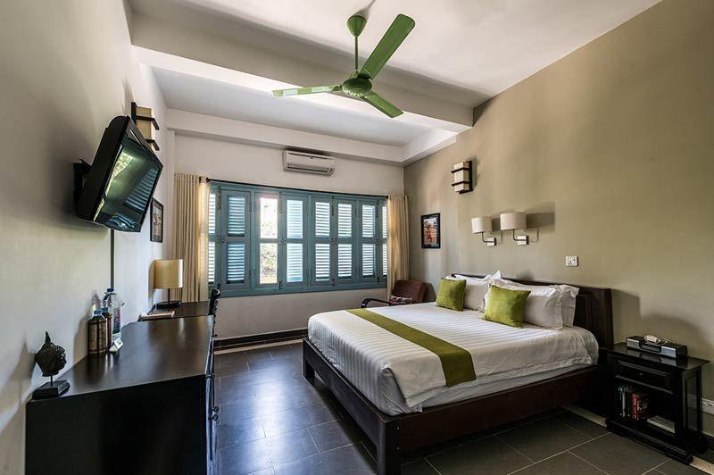 slaapkamer met blauwe luikjes voor raam - The Columns Kampot - Cambodja