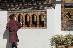 man draait aan gebedsmolens in Bhutan