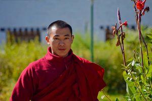 monnik met rode bloem in Bhutan - Bhutan
