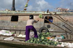 Vietnam - Mekong Delta - vrouw gooit groente op drijvende markt