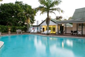 zwembaden met palmen - Tsitsikamma Village Inn - Zuid-Afrika